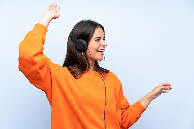 Musica d'ascolto della giovane donna con un cellulare e ballare sopra la parete blu isolata