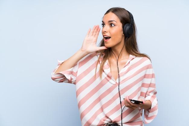 Musica d'ascolto della giovane donna con un cellulare sopra la parete blu isolata che grida con la bocca spalancata