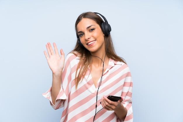 Musica d'ascolto della giovane donna con un cellulare sopra la parete blu isolata che saluta con la mano con l'espressione felice