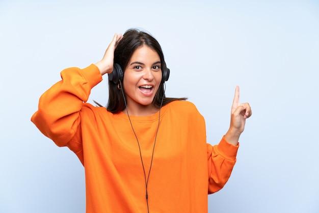 Musica d'ascolto della giovane donna con un cellulare sopra la parete blu isolata sorpresa e indicando dito il lato
