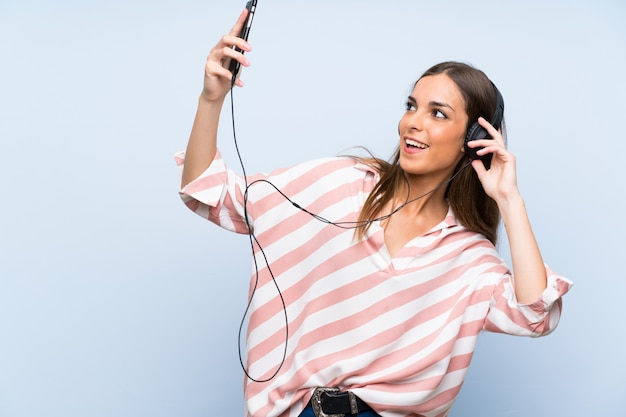 Musica d'ascolto della giovane donna con un cellulare sopra la parete blu isolata