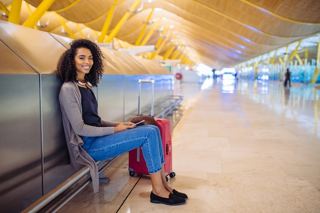 Musica d'ascolto della giovane donna di colore felice con le cuffie e il telefono cellulare all'aeroporto