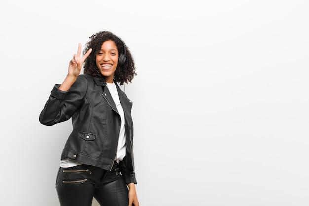 Musica d'ascolto della giovane donna di colore graziosa con cuffie che indossano una giacca di pelle contro il muro bianco