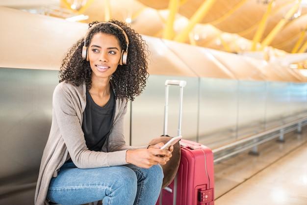 Musica d'ascolto della giovane donna felice con le cuffie e il telefono cellulare all'aeroporto