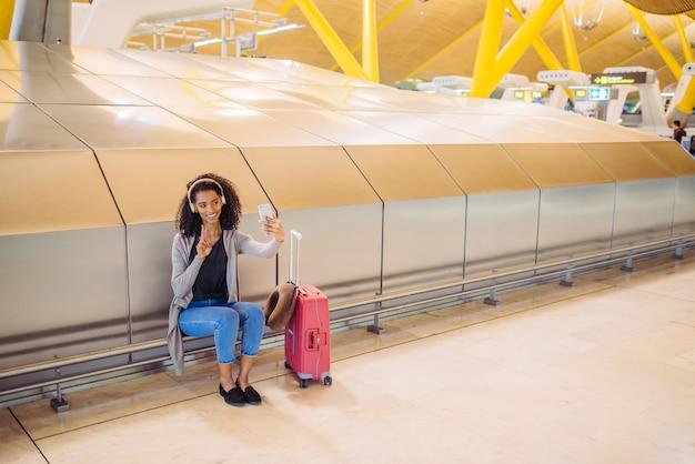 Musica d'ascolto della giovane donna felice con le cuffie e prendere selfie con il telefono cellulare all'aeroporto