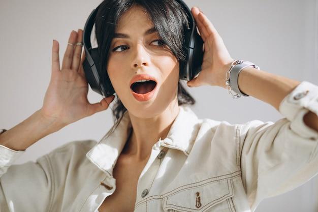 Musica d'ascolto della giovane donna graziosa sulle cuffie senza fili