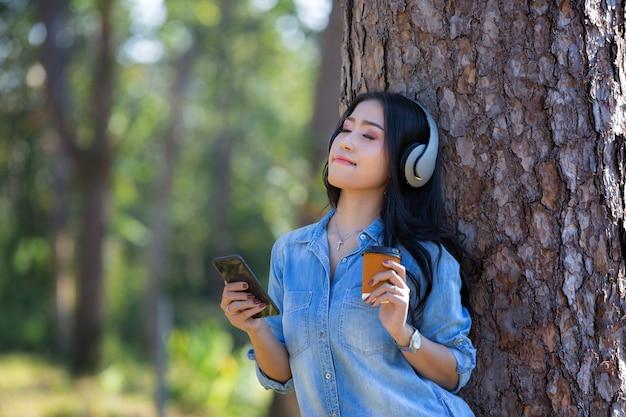 Musica d'ascolto della giovane donna in cuffie moderne che comunicano online con la tazza di caffè