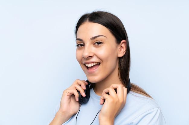 Musica d'ascolto della giovane donna sopra la parete blu isolata
