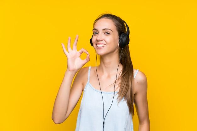 Musica d'ascolto della giovane donna sopra la parete gialla isolata che mostra segno giusto con le dita