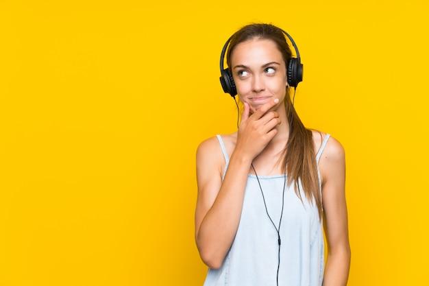 Musica d'ascolto della giovane donna sopra la parete gialla isolata che pensa un'idea