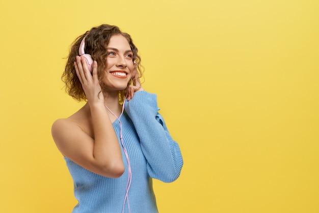 Musica d'ascolto della ragazza allegra con le cuffie, sorridenti.