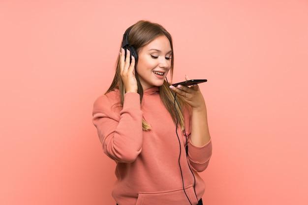 Musica d'ascolto della ragazza dell'adolescente con un cellulare sopra fondo rosa isolato