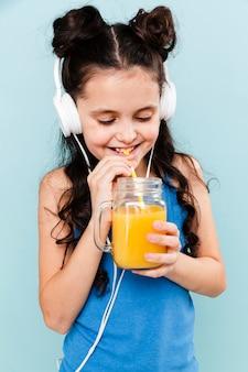 Musica d'ascolto della ragazza e bere succo