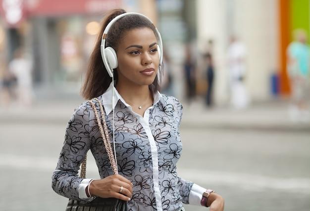 Musica d'ascolto della ragazza graziosa con le sue cuffie sulla via