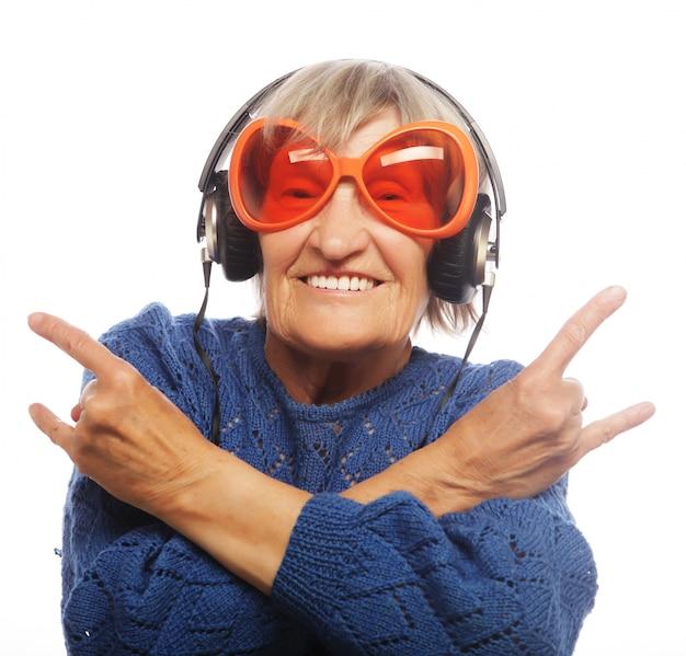 Musica d'ascolto della signora anziana divertente e mostrare i pollici su.