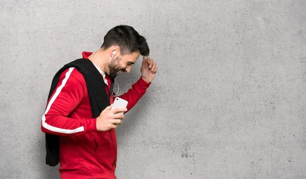 Musica d'ascolto dello sportsman bello con il telefono sopra la parete strutturata