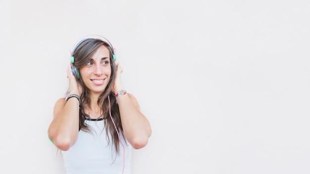 Musica d'ascolto sorridente della donna sulla cuffia contro fondo bianco