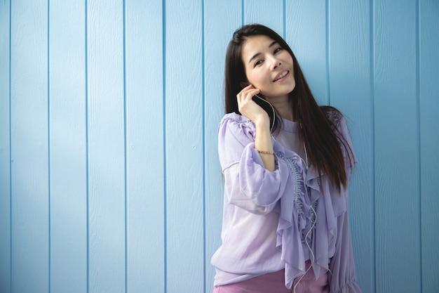 Musica d'ascolto sorridente della giovane donna asiatica con struttura di legno blu. giovane donna asiatica stile di vita.