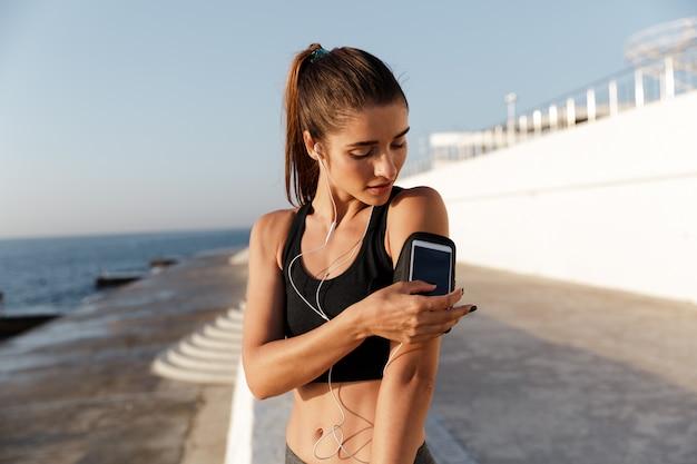 Musica d'ascolto sorridente della giovane donna di sport facendo uso del telefono cellulare.
