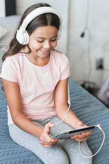 Musica d'ascolto sorridente della ragazza sulla cuffia tramite la compressa digitale