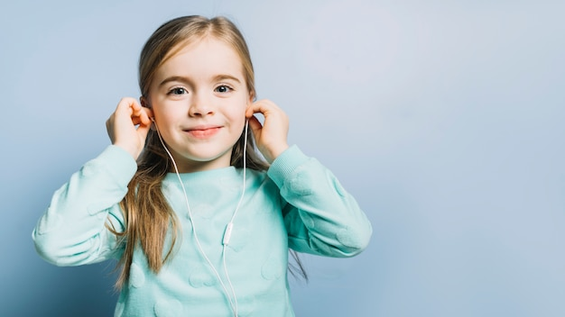 Musica d'ascolto sorridente della ragazza sveglia sulle cuffie contro fondo blu