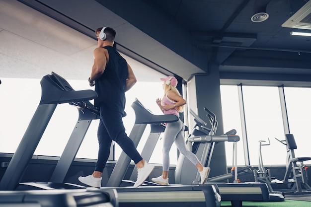 Musica ed esercizi vanno insieme. esercizio di lavoro delle coppie sul tapis roulant. l'attenzione è rivolta all'uomo.