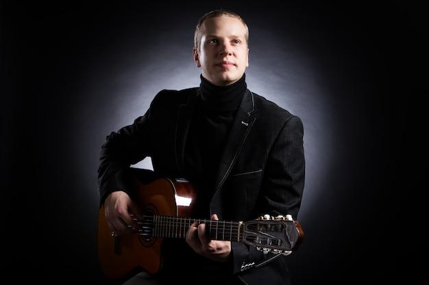Musica. giovane musicista in abito nero in possesso di una chitarra