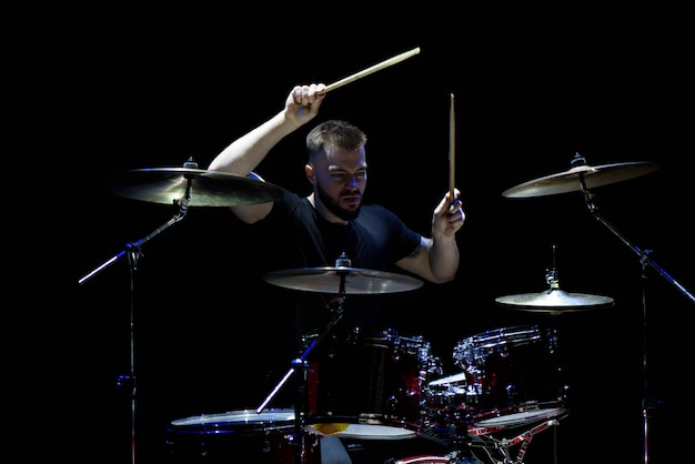 Musica, persone, strumenti musicali e concetto di intrattenimento - musicista maschio con bacchette che suona la batteria e piatti al concerto o in studio