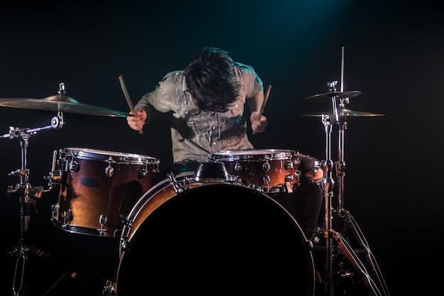 Musicista che suona la batteria, sfondo nero e bella luce soffusa, gioco emotivo, concetto di musica