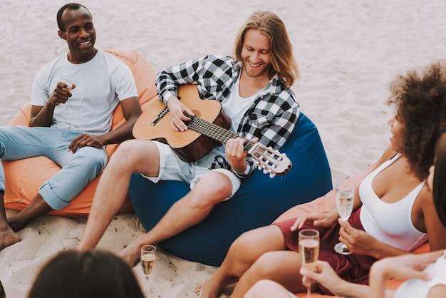 Musicista che suona la chitarra sulla spiaggia per gli amici