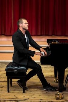 Musicista di seduta di vista laterale che gioca piano