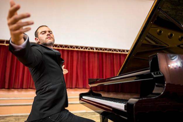Musicista di vista bassa che diffonde le mani nell'aria