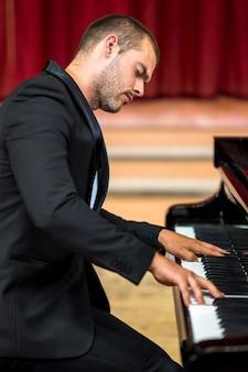 Musicista di vista laterale che suona il pianoforte