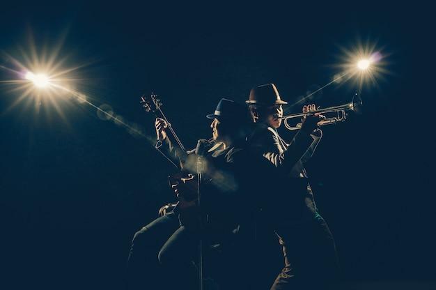 Musicista duo band suona una tromba e canta una canzone e suona la chitarra su sfondo nero wi
