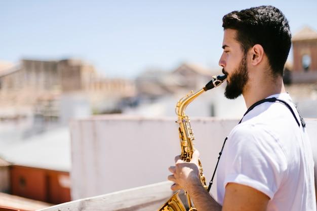 Musicista lateralmente che suona il sassofono