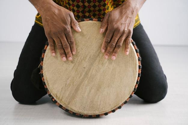 Musicista maschio afroamericano che gioca i tamburi tradizionali a casa. concetto di classe di musica online. strumenti musicali per il tempo libero e l'apprendimento. ritmo nelle tradizioni etniche multiculturali.