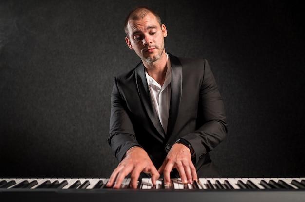 Musicista vestito elegante che suona le tastiere vista frontale