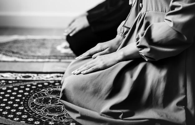 Musulmani che pregano nella postura di tashahhud