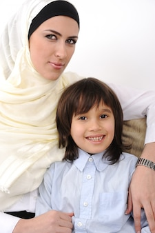 Musulmano e figlio coperti arabi musulmani che si rilassano a casa