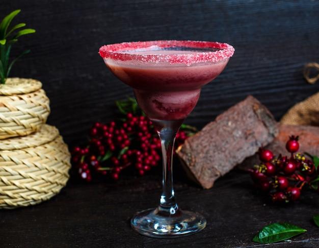 Ñ bere il mirtillo in un bicchiere coperto di sabbia rosa