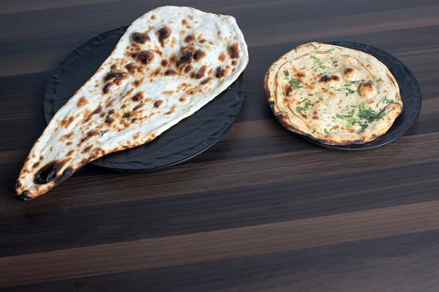Naan e tandoori roti in un tavolo di legno