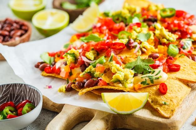 Nachos con salsa di formaggio, guacomole, salsa e verdure sul tavolo. concetto di cibo per feste.