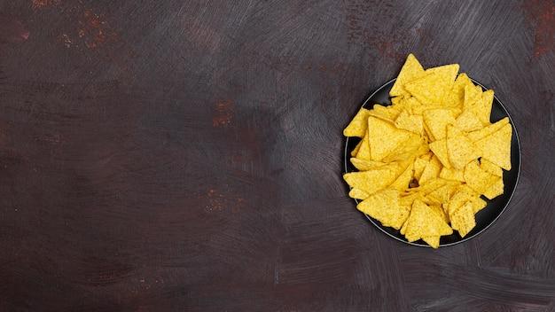 Nachos in ciotola nera su fondo marrone