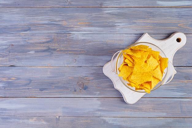 Nachos messicani con formaggio. chip di mais isolati sulla tavola di legno