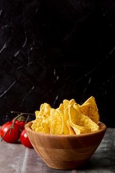 Nachos saporiti in ciotola e pomodori di legno