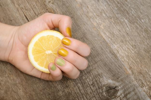 Nail design giallo. mano femminile con glitter manicure in possesso di limone.