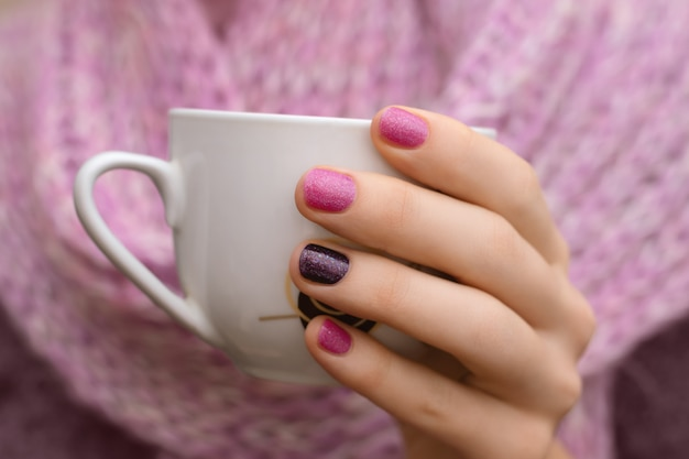 Nail design rosa. mano femminile che tiene tazza bianca.