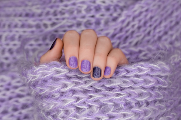 Nail design viola. mano femminile ben curata su sfondo viola.