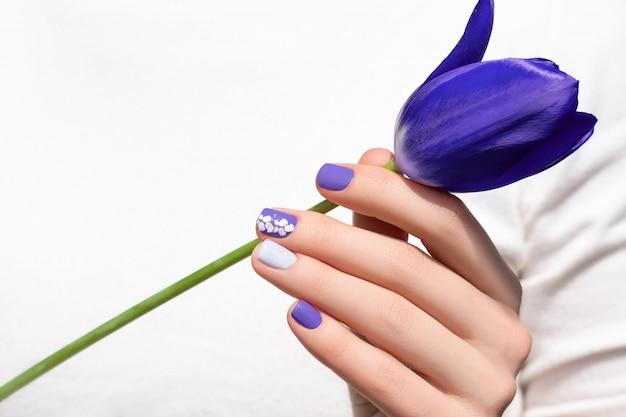 Nail design viola. mano femminile con il fiore viola del tulipano della tenuta del manicure