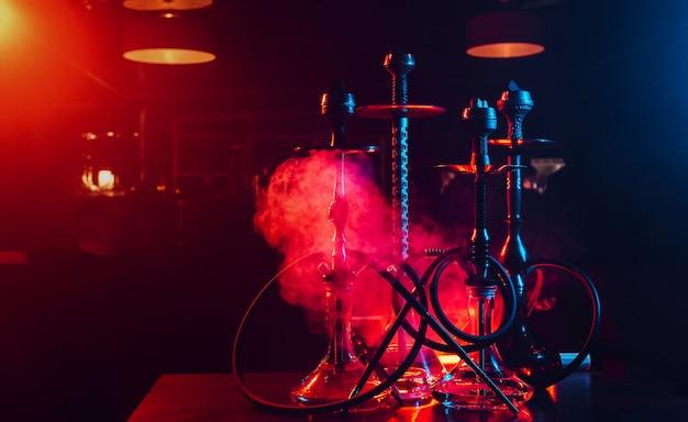 Narghilè con boccette di vetro shisha e ciotole di metallo con carboni per il relax